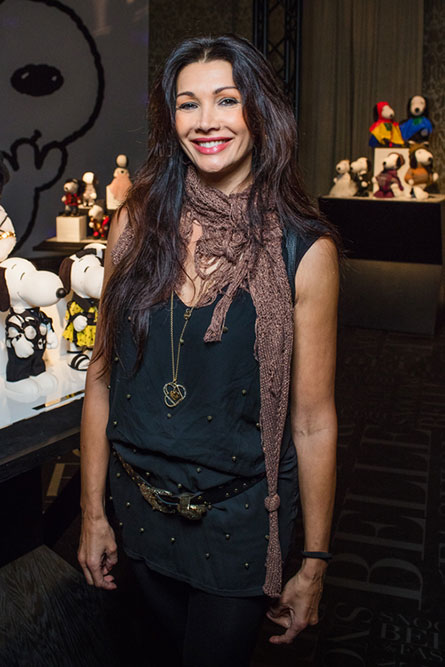 A tall, brunette woman wearing a black top and a brown scarf, smiling and posing for a photo at an event.