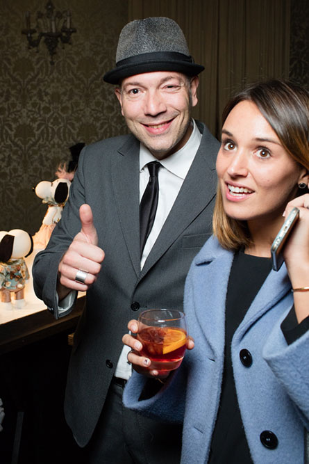 A man and a woman at a semi-formal event. The man is wearing a grey suit, a hat and giving a thumbs up. The girl is wearing a blue jacket and holding a cocktail in her hand.