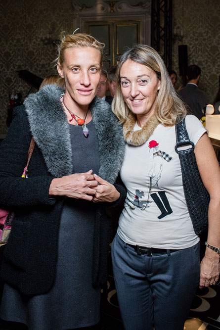 Two blonde women posing for a phot at a semi-formal event. The woman on the left is wearing a blue coat and the woman on the right is in a white t-shirt.