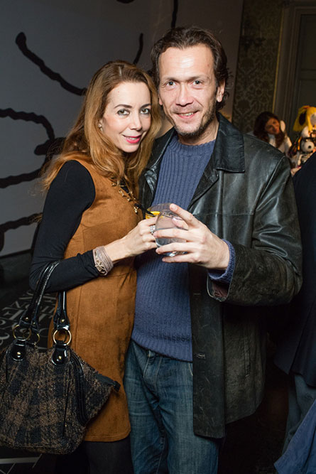 A middle-aged woman wearing a brown dress is standing beside a man wearing a black leather jacket and posing for a photo at an event.