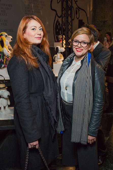 A woman with red hair and a black jacket is standing next to a woman with short hair wearing a black jacket and black and white scarf. They are posing for a photo at a semi formal event.