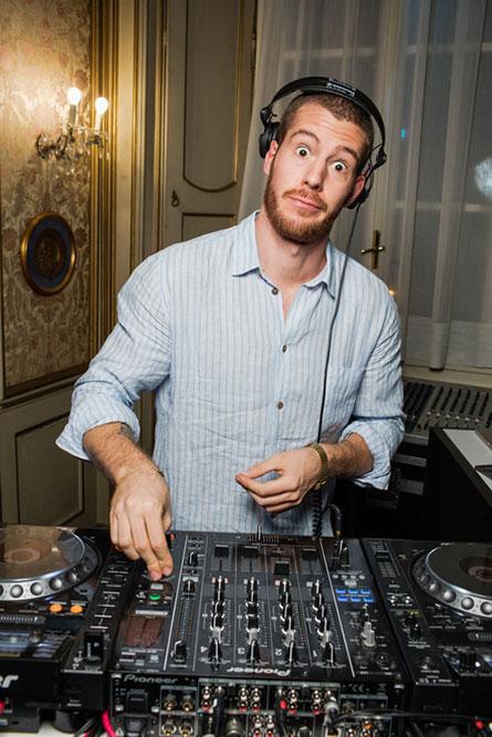 A male DJ, wearing a light blue shirt, making a funny face.