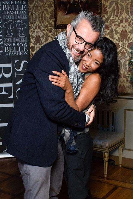 A man with grey hair, wearing a black suit and a grey scarf, is leaning over and hugging a woman. They are posing for a photo at an event.