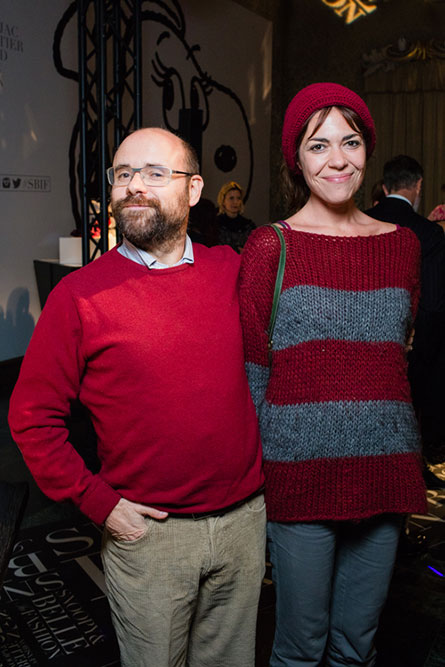 A bald, bearded man, wearing a red sweater is posing for a photo beside a tall woman wearing a red and grey striped sweater.