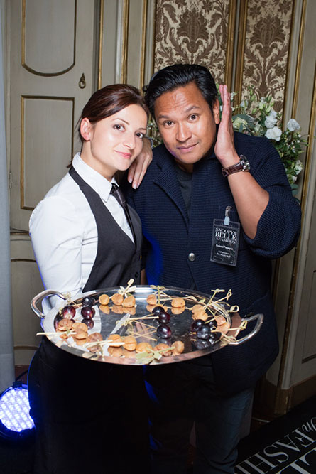 A female waitress holding a food tray is leaning against a man wearing a blue suit and posing for a photo.