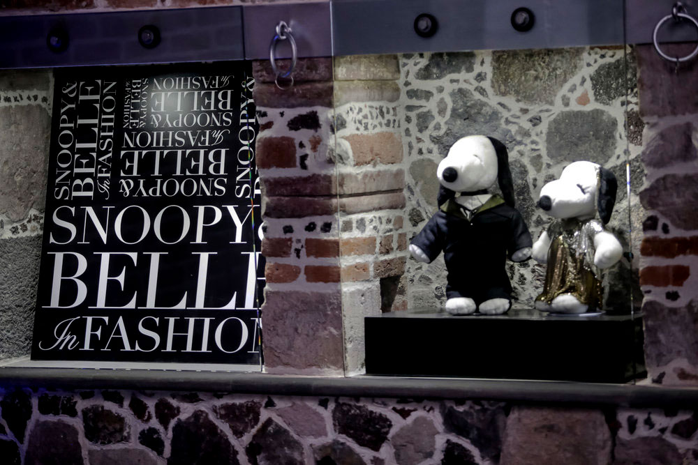 A brick wall and a glass display of two black and white dogs wearing elaborate clothes and a black and white poster beside them.
