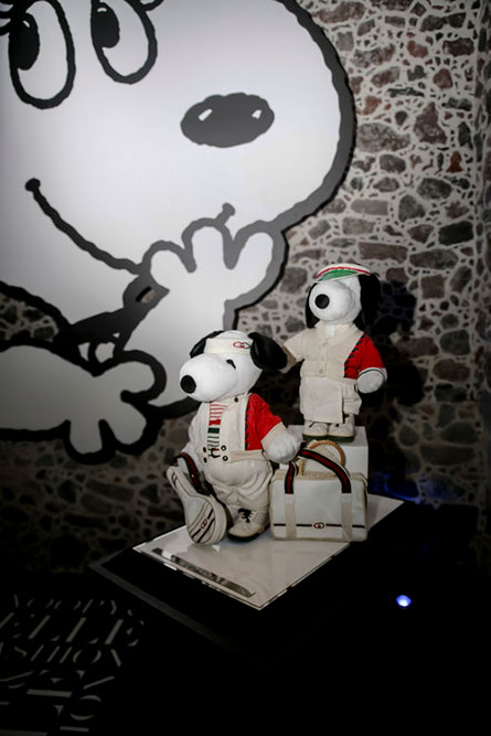 A dark indoor space with a display of two black and white dogs wearing red and white outfits.
