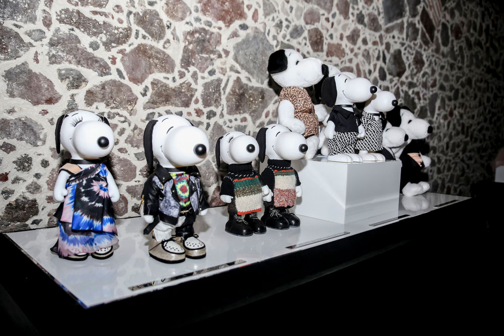 A display of black and white dog statues, wearing various outfits, in front of a brick wall.