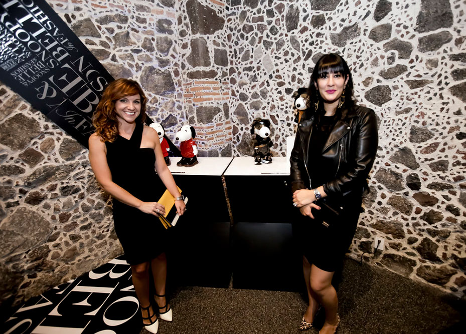 Two women, wearing cocktail dresses, posing in front of a display showcasing two black and white dog statues.