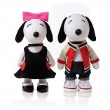 Two black and white dog statues in front of a white background. The dog on the left is wearing a black dress and a pink bow on her head. The dog on the right is wearing a red and white jacket with black pants.