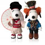 Two black and white dog statues in front of a white background. The dog on the left is wearing a Japanese kimono and holding an umbrella. The dog on the right is wearing an orange wig, a dark blue tuxedo and a black top hat.